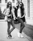 Fashion shot of two elegant beautiful girls in the sunset wearing sunglasses, fur vests . Two young women outdoor on the street. Shopping inspiration. Monochrome (black and white)  photo — Stock Photo
