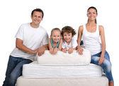 Family and many mattresses — Stock Photo