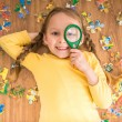 Girl with puzzle and loupe — Stock Photo #71730469