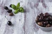 Olive nere in salamoia in una ciotola su fondo di legno. — Foto Stock