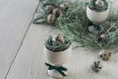 Easter eggs in a ceramic holder on linen napkin on wooden background.Selective focus. — Stock Photo