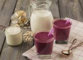 Smoothie made with frozen red berries,milk, and oatmeal in a glasses in wooden background.Selective focus. — Stock Photo