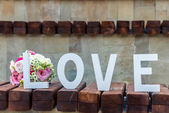 Bouquet of flowers and an inscription love — Stock Photo