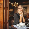 Woman in cafe with laptop taking notes — Stock Photo #55201459