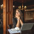 Woman in cafe with laptop taking notes — Stock Photo #55201465