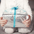 Baby holds a Christmas present box in hands — Stock Photo #61150141