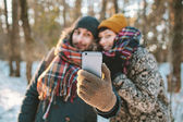 Couple making selfie in winter forest — Stock Photo