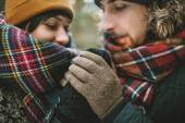 Young man holds his girlfriends hands in winter forest — Stock Photo