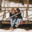 Young couple sitting on wooden bridge in winter forest — Stock Photo #65628579