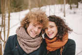 Portrait of young smiling couple with curly hair in winter fores — Stock Photo