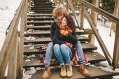 Young couple sitting on wooden stairs outdoors in winter — Stock Photo