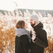 Happy hipster couple hugging near winter lake and reeds — Stock Photo #66556495