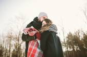 Young couple in winter forest with plaid and thermos — Stock Photo