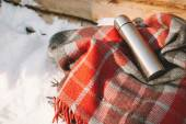 Plaid and thermos on snow near wooden wall — Stock Photo