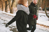 Hipster couple running in winter park looking at each other — Fotografia Stock