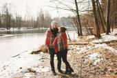 Couple looking each other near winter lake under plaid — Stock Photo