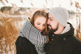 Happy hipster couple hugging near winter lake and reeds — Stockfoto