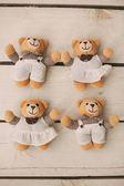 Four teddy bears on wooden background — Stock Photo