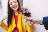 Woman clinking red wine glass with man outdoors — Stock Photo