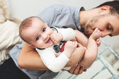 Young happy father kissing smiling baby in leg — Stock Photo