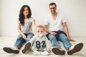 Young hipster father, mother and baby boy on wooden floor — Stok fotoğraf
