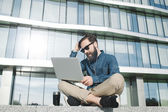 Businessman in sunglasses with laptop holding head outdoors — Stock Photo