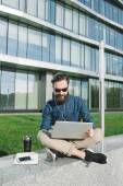 Businessman in sunglasses with laptop outdoors in front of offic — Stock Photo