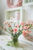 Beautiful pink flowers in a vase on white rustic table — Stock Photo