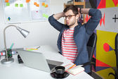 Stressed young male in modern office with laptop — Stock Photo