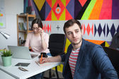 Young male discussing business with woman in modern office — Stock Photo