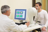 Man having his eyes examined by an eye elderly doctor. — Stock Photo