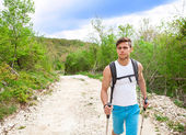 Sporty hiker walking through forest — Stock Photo