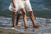 Happy couple in love walking on the beach — Stock Photo