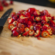 Cut rosehips on chopping board with knife — Stock Photo #53750491