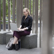 Young business woman sitting outside with laptop — Stock Photo #53755195