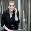 Young business woman sitting outside with laptop and mobile phon — Stock Photo #53759061