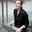Young business woman sitting outside with laptop and mobile phon — Stock Photo #53759811