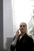 Young business woman speaking on mobile phone looking at the cam — Stock Photo