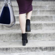 Feet and legs of woman walking up steps — Stock Photo #53767555