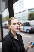 Woman waiting at bus stop with mobile phone in London — Stock Photo