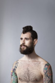 Studio portrait of young man with beard and tattoos — Stock Photo