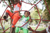 Girl on climbing frame with mother and sister — Stock Photo