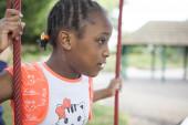Young girl with dark skin climbing on playground — Zdjęcie stockowe