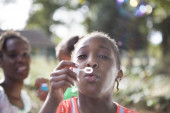Child with dark skin blowing soap bubbles — Stok fotoğraf