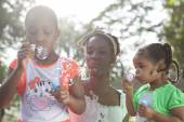 Family with dark skin playing with soap bubbles — Stock Photo