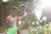 Family of African descent in park smelling flowers — Stock Photo