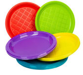 Bright plastic tableware stacked isolated on white — Stock Photo