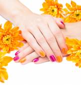 Women's hands with bright manicure and flowers around — Stockfoto