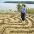 The girl thoughtfully walks through the maze on the banks of the river. — Stock Photo #57654327