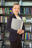 Business woman in a jacket with a folder in hands in a library — Stockfoto